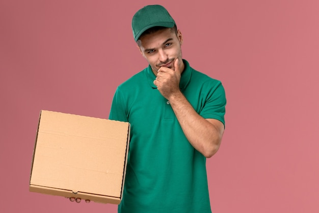 Courier masculino de uniforme verde segurando uma caixa de comida e pensando no fundo rosa