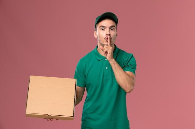 Courier masculino de uniforme verde segurando uma caixa de comida pedindo para ficar em silêncio sobre um fundo rosa