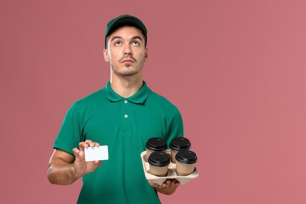 Courier masculino de uniforme verde segurando xícaras de café marrons e cartão no fundo rosa