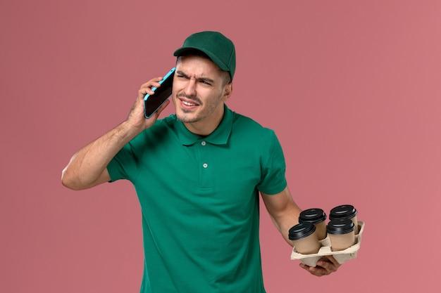 Courier masculino de uniforme verde segurando xícaras de café marrons e falando ao telefone no fundo rosa.