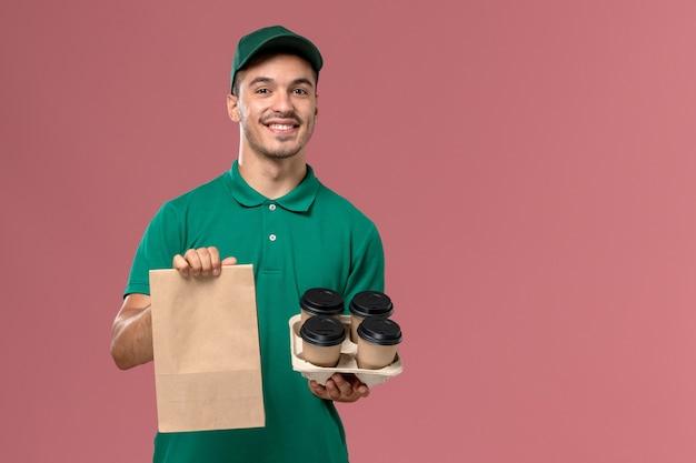 Courier masculino de uniforme verde segurando xícaras de café marrons e um pacote de comida sorrindo no fundo rosa