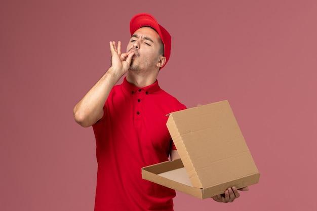 Courier masculino de uniforme vermelho e capa segurando a caixa de comida na parede rosa.