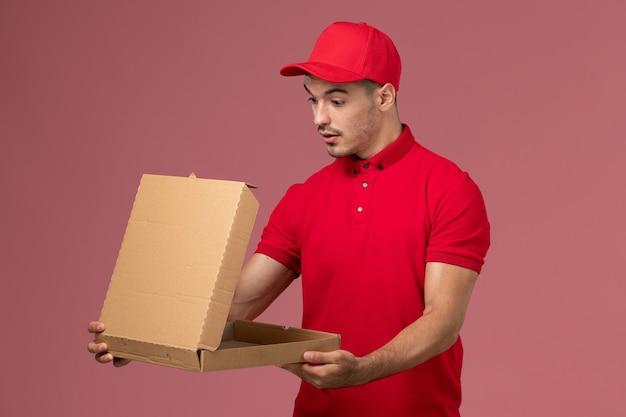 Courier masculino de uniforme vermelho e capa segurando a caixa de entrega de comida na parede rosa.