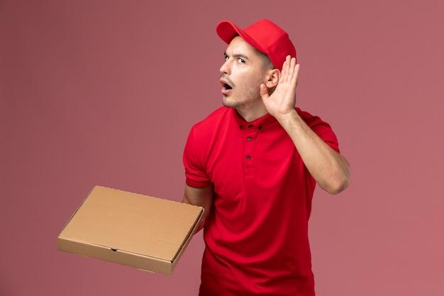 Courier masculino de uniforme vermelho e capa segurando a caixa de entrega de comida, tentando ouvir na parede rosa