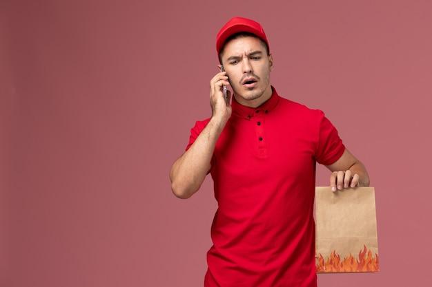Courier masculino de uniforme vermelho e capa segurando o pacote de comida e falando ao telefone na parede rosa