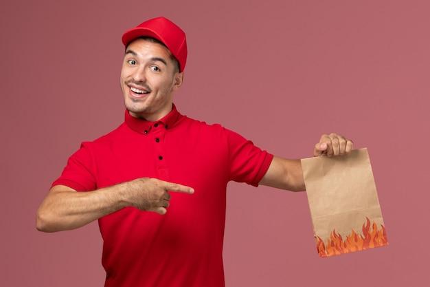 Courier masculino de uniforme vermelho e capa segurando um pacote de comida com um sorriso na parede rosa