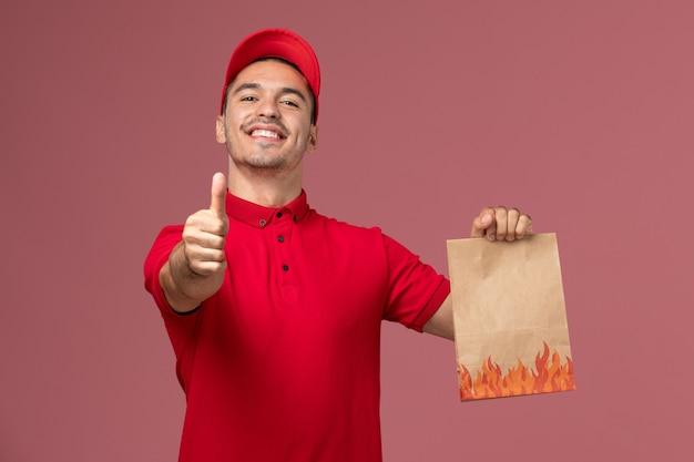 Courier masculino de uniforme vermelho e capa segurando um pacote de comida de papel, sorrindo na parede rosa