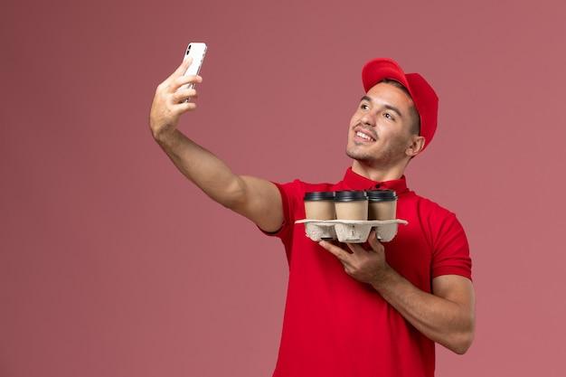 Courier masculino de uniforme vermelho e capa segurando xícaras de café e tirando foto na parede rosa