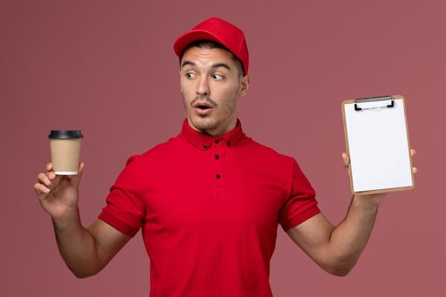 Courier masculino de uniforme vermelho segurando a xícara de café de entrega e o bloco de notas na parede rosa.
