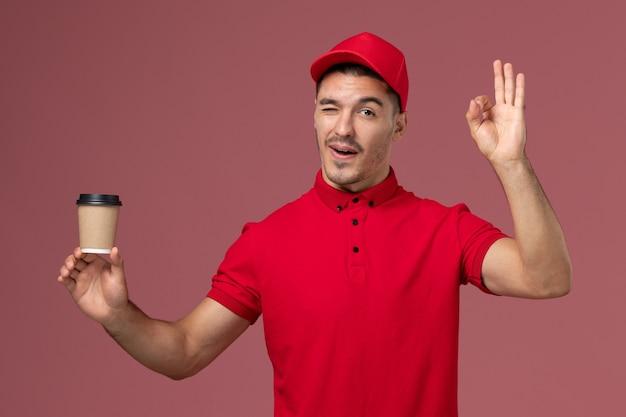 Courier masculino de uniforme vermelho segurando a xícara de café de entrega e piscando na parede rosa trabalhador masculino
