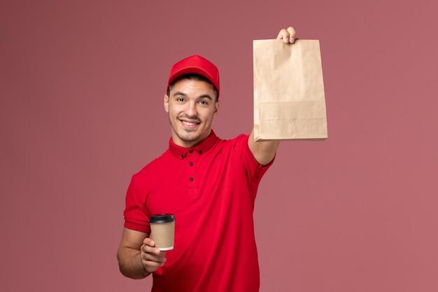 Courier masculino de uniforme vermelho segurando a xícara de café de entrega e um pacote de comida com um sorriso na parede rosa.