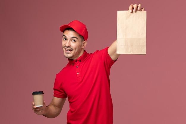 Courier masculino de uniforme vermelho segurando uma xícara de café de entrega e um pacote de comida na parede rosa.
