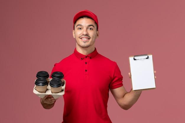 Courier masculino de uniforme vermelho segurando xícaras de café de entrega com um bloco de notas sorrindo