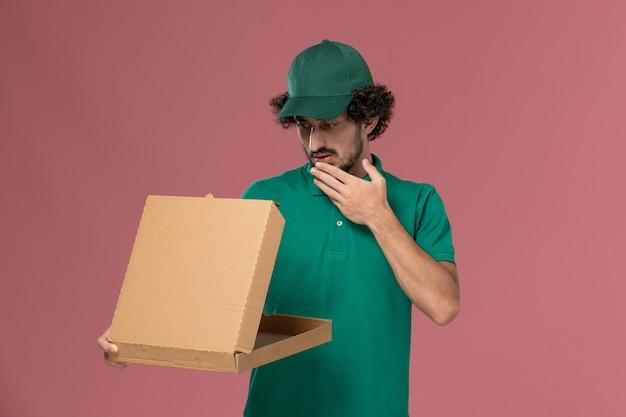 Courier masculino de vista frontal com uniforme verde e capa segurando e abrindo a caixa de entrega de comida no fundo rosa.