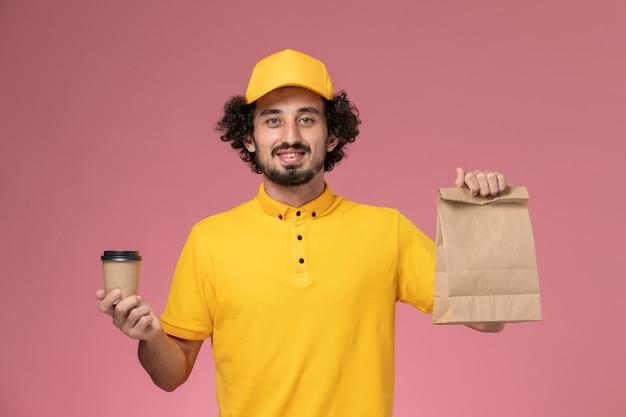 Courier masculino de vista frontal em uniforme amarelo e capa segurando a xícara de café de entrega e pacote de comida na mesa rosa uniforme serviço empresa trabalho trabalhador masculino