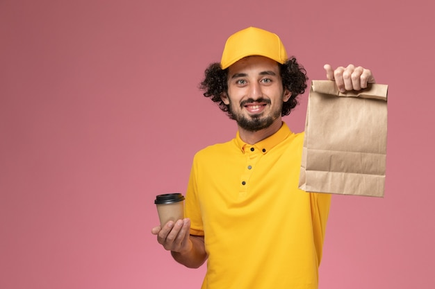 Courier masculino de vista frontal em uniforme amarelo e capa segurando a xícara de café de entrega e pacote de comida na mesa rosa uniforme trabalho serviço empresa trabalhador masculino
