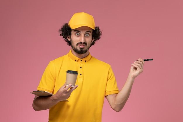 Courier masculino de vista frontal em uniforme amarelo e capa segurando caneta xícara de café de entrega e bloco de notas na mesa rosa uniforme serviço empresa trabalho trabalhador masculino