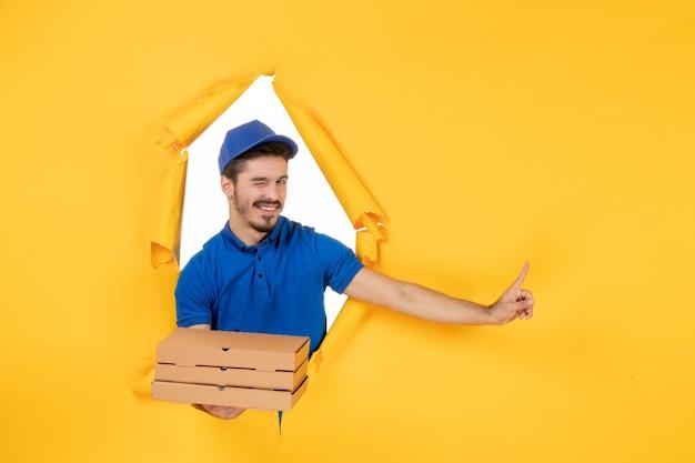 Courier masculino segurando caixas de pizza na mesa de cor amarela. trabalhador entrega trabalho trabalho serviço comida uniforme