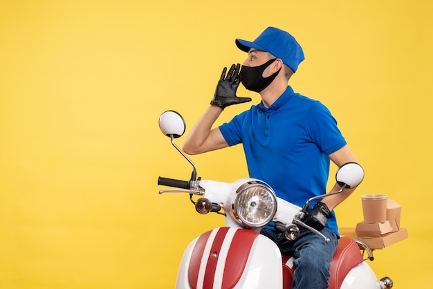 Courier masculino sentado em uma bicicleta, mascarado, chamando alguém no serviço de trabalho amarelo, pandemia, entrega, covid, uniforme, emprego