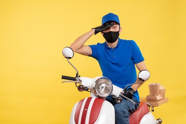 Courier masculino sentado em uma bicicleta, mascarado em amarelo serviço de trabalho covid - uniforme de trabalho pandemia