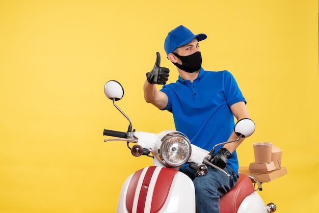 Courier masculino sentado em uma bicicleta, mascarado em amarelo trabalho entrega covid - pandemia de emprego uniforme