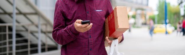 Courier usando um telefone para pesquisar o caminho do endereço para entregar pacotes