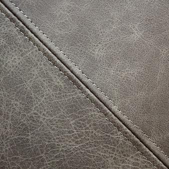 Couro cinza de textura com costura decorativa diagonal, fundo close-up