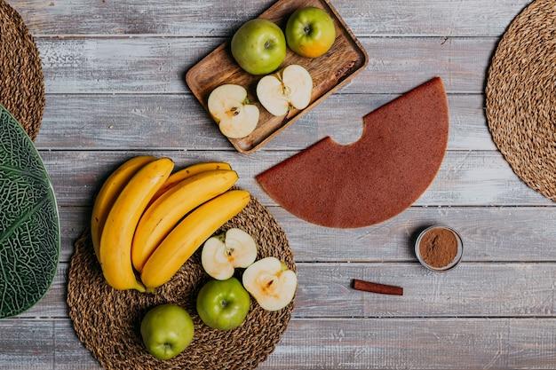 Couro da fruta canela com frutas frescas na mesa de madeira. couro redondo de frutas. comida saudável. vista superior de maçãs, bananas e paus de canela.