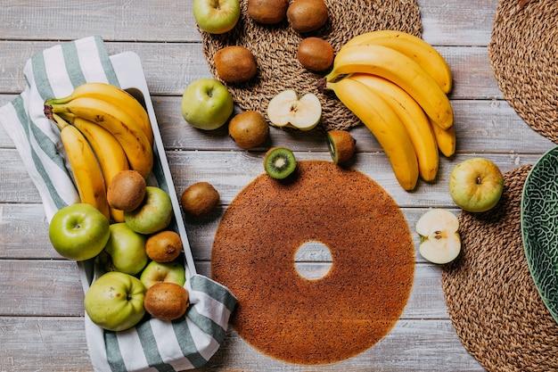 Couro de frutas com frutas frescas na mesa de madeira. couro redondo de frutas. comida saudável. vista superior das maçãs, bananas e kiwis.
