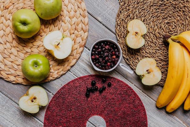 Couro de frutas de groselha preta com frutas frescas na mesa de madeira. couro redondo de frutas vermelhas com groselha preta. comida saudável. maçãs, bananas, vista superior.