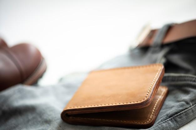 Couro e acessório da carteira do couro do nobuck de brown isolados no fundo branco. foco seletivo
