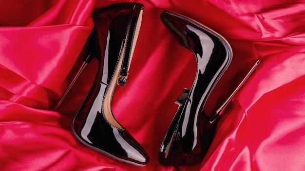 Couro envernizado brilhante preto fetiche salto alto com tira no tornozelo em fundo de cetim vermelho