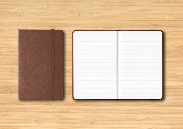 Couro escuro fechado e maquete de cadernos forrados aberta isolada em fundo de madeira