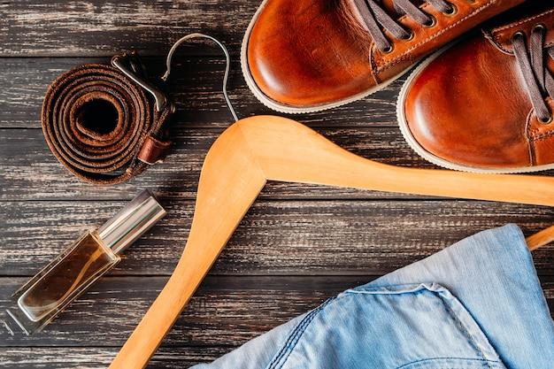 Couro marrom sapatos casuais jeans, cinto e perfume na vista superior de madeira escura