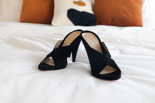 Couro preto peep-toe sandálias de salto na cama branca