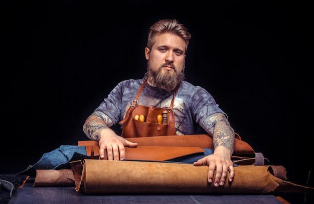 Couro profissional que trabalha com couro usando ferramentas de artesanato.