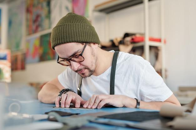 Couro profissional usando chapéu e camiseta curvando-se sobre a mesa enquanto mede um pedaço de couro ou camurça no trabalho