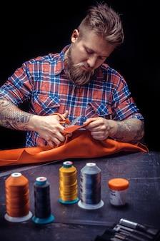 Couro skinner trabalhando com couro usando ferramentas de artesanato