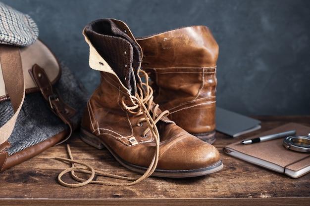 Couro velho para viagem, botas vintage, sapatos e bolsa na mesa de madeira, com textura de fundo de parede
