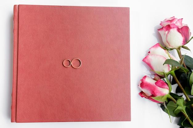 Couro vermelho livro ou álbum de casamento coberto com duas alianças de casamento e três rosas encontra-se no fundo branco.