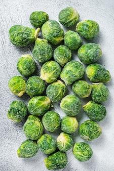 Couve de bruxelas congelada repolho verde na mesa da cozinha. fundo branco. vista do topo.