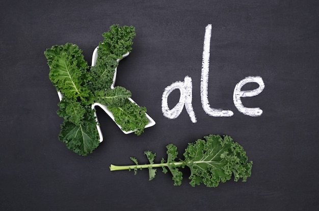 Couve de couve de folhas encaracoladas dentro da letra k em forma de placa, inscrição de giz kale no quadro-negro. comida saudável