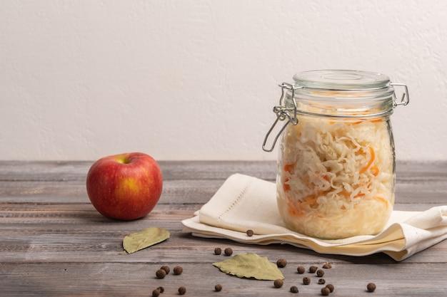 Couve enlatada caseira em pote no guardanapo de linho com maçã, pimenta e folhas de louro em uma mesa de madeira. fechar-se. copie o espaço