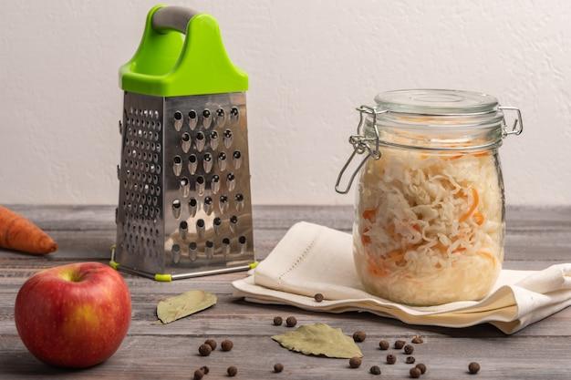 Couve enlatada caseira em pote no guardanapo de linho com maçã, pimenta e folhas de louro em uma mesa de madeira. perto de ralador e cenouras. fechar-se. copie o espaço