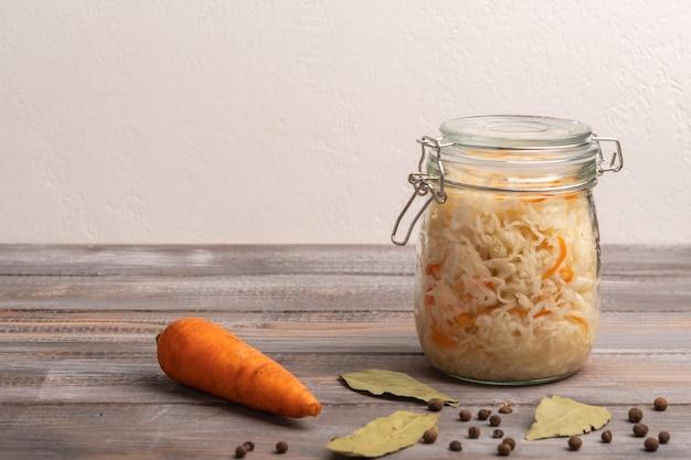 Couve enlatada caseira em potes com cenoura, pimenta do reino e folhas de louro em uma mesa de madeira. fechar-se. copie o espaço