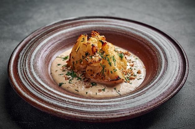 Couve-flor caseira assada em molho de queijo gruyere, ervas e azeite de oliva em um prato de cerâmica sobre uma superfície escura