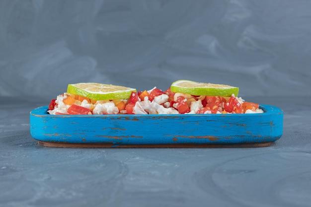 Couve-flor, cenoura e pimenta misturadas em uma salada e cobertas com rodelas de limão na mesa de mármore.