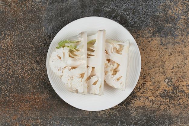Couve-flor fatiada gostosa no prato, na superfície do mármore