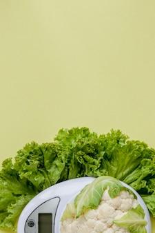 Couve-flor orgânica em um vaso em um amarelo. alimentação saudável, planejamento de dieta, perda de peso, desintoxicação, agricultura orgânica.