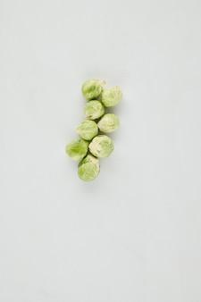 Couves de bruxelas maduras frescas para um prato saudável na mesa cinza claro